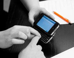 Bild på LVI-handledare och deltagare med en iPhone smarttelefon med punkttangentbord.